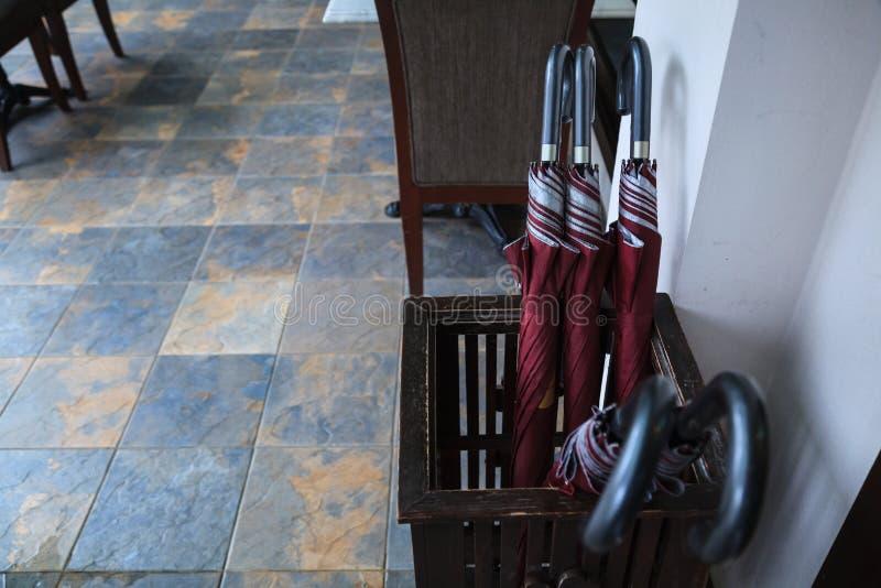Parapluies ultra-violets de protection de grand velours rouge fort dans le panier en bois prêt à employer pour l'abri provisoire  photographie stock