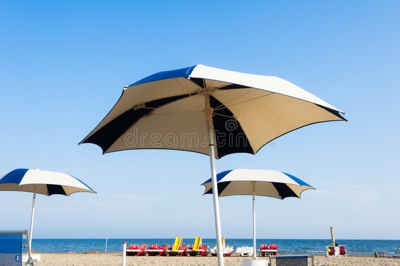 Paraplustrand voor het ontspannen en zon vastgesteld strand stock afbeeldingen