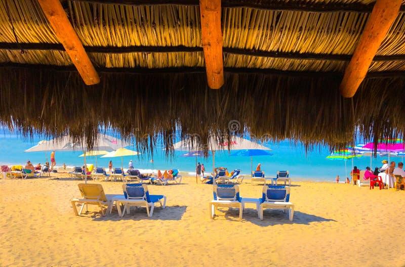 Paraply för Palapa sugrörkoja på den tropiska stranden fotografering för bildbyråer