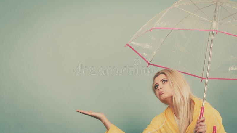 Paraply för regnrock för kvinna som bärande hållande kontrollerar väder royaltyfria bilder