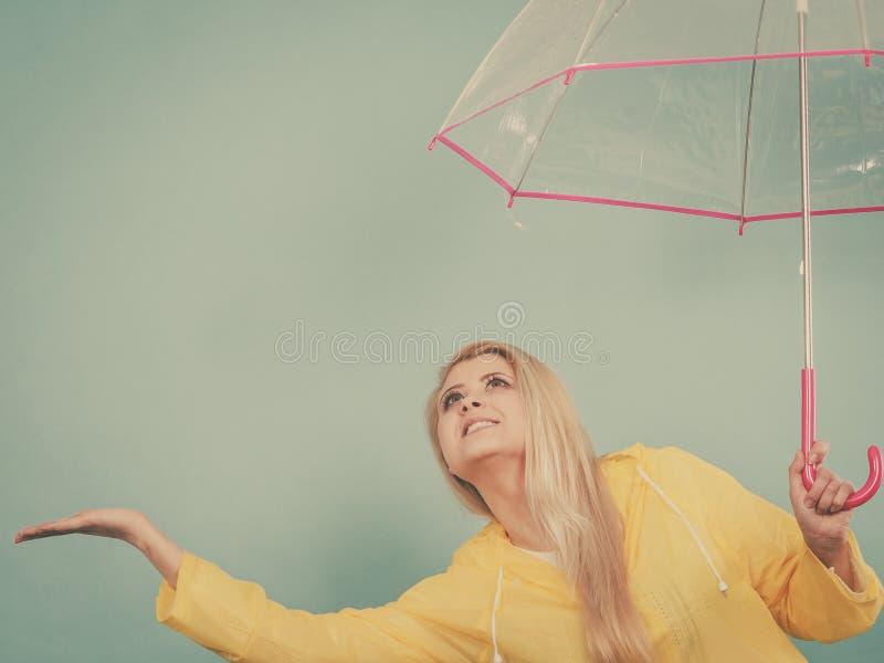 Paraply f?r regnrock f?r kvinna som b?rande h?llande kontrollerar v?der arkivfoto