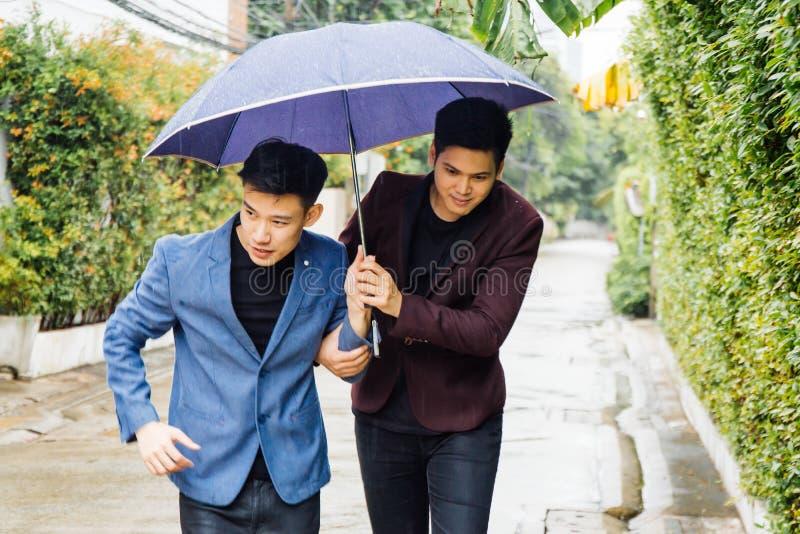 Paraply och händer för glade par hållande tillsammans Asiatiska homosexuella män som går i regnet royaltyfri fotografi