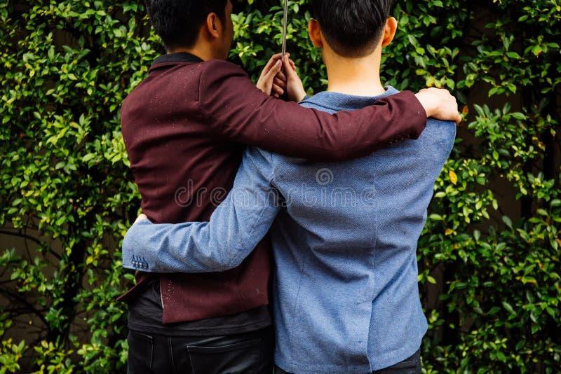 Paraply och händer för glade par hållande tillsammans Dra tillbaka av homosexuella män som går i regnet royaltyfri bild