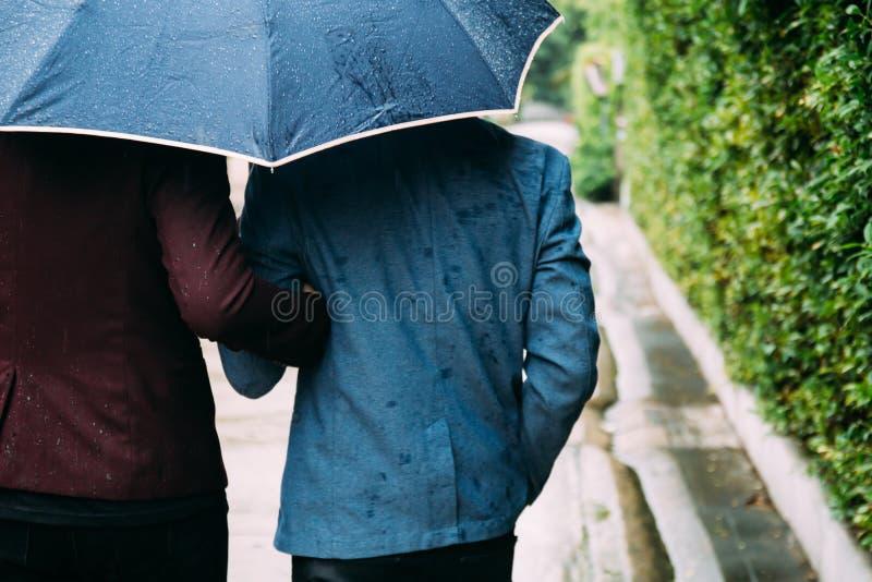 Paraply och händer för glade par hållande tillsammans Dra tillbaka av homosexuella män som går i regnet fotografering för bildbyråer