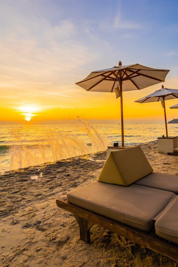 Paraply och stol med kudden runt om h?rligt landskap av stranden och havet fotografering för bildbyråer