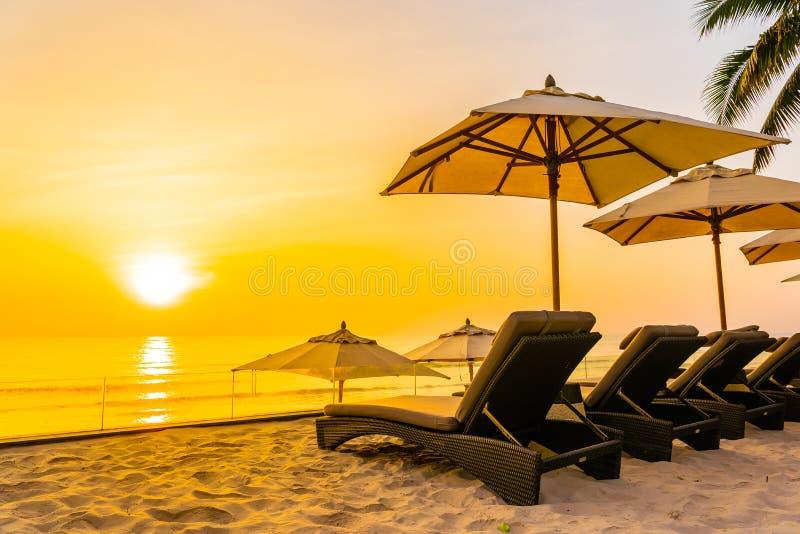 Paraply och stol p? den h?rliga stranden och hav p? soluppg?ngtid f?r lopp och semester arkivbilder