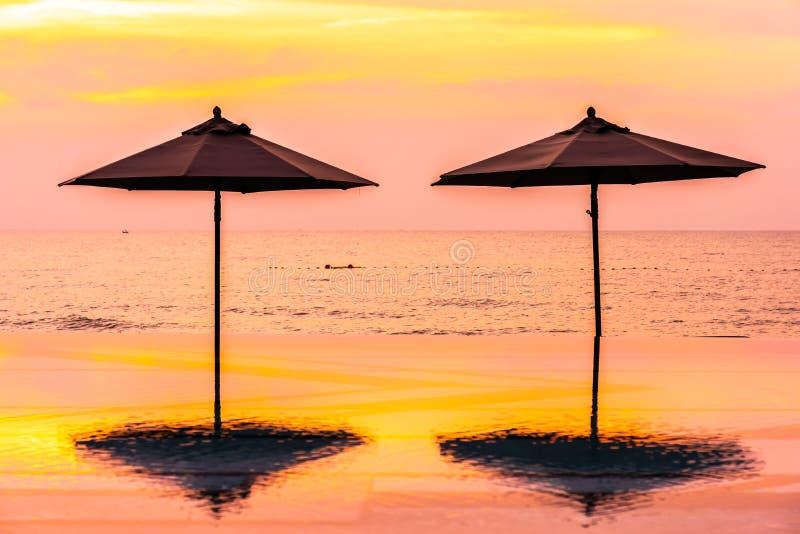 Paraply och stol runt om för havshav för simbassäng den neary stranden på soluppgång- eller solnedgångtid arkivfoton