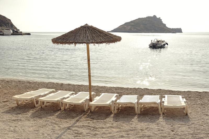 Paraply och tomma sunbeds på den sandiga stranden under semester arkivfoto