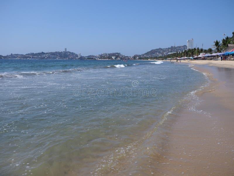 Paraplyer och exotiskt gömma i handflatan på den sandiga stranden på fjärden av det Acapulco stadslandskapet med vågor av Stilla  royaltyfria foton
