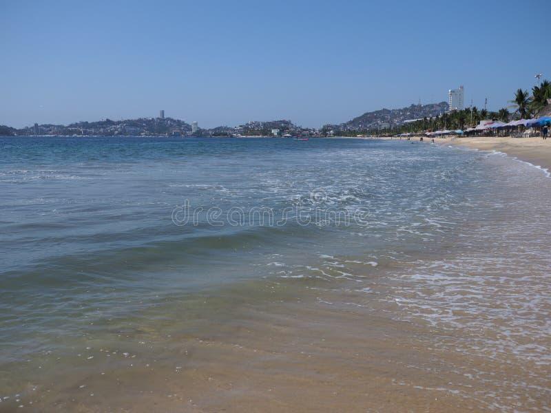 Paraplyer och exotiskt gömma i handflatan på den sandiga stranden på skönhetfjärden av det Acapulco stadslandskapet med vågor av  arkivfoton