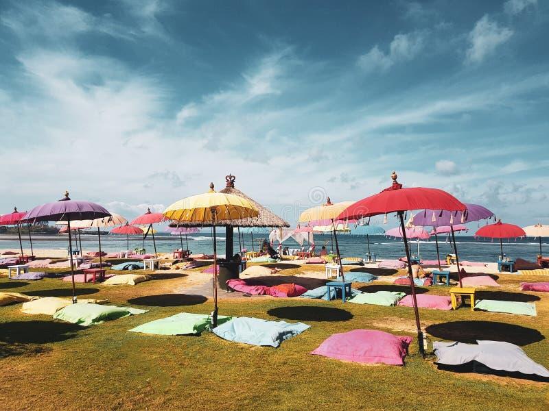 Paraplyer och stora kuddeplatser på stranden arkivbild