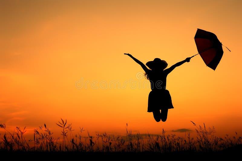 Paraplykvinnabanhoppning och solnedgångsilhouette royaltyfri bild