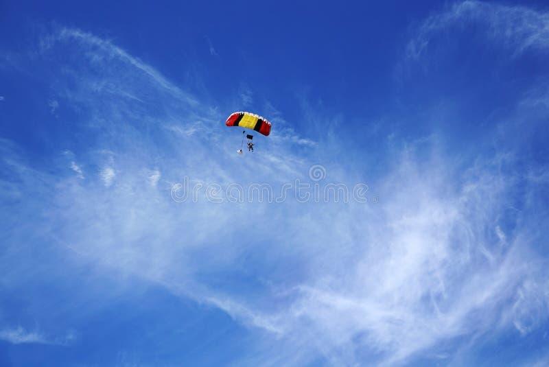 Paraquedas vermelho-amarelo multicolorido com as silhuetas skydivers AG imagem de stock