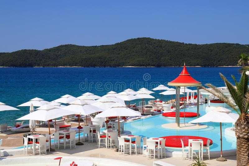 Parasóis cênicos bonitos da opinião da praia do verão, os brancos e os vermelhos perto da associação luxuosa Deckchairs brancos d fotografia de stock