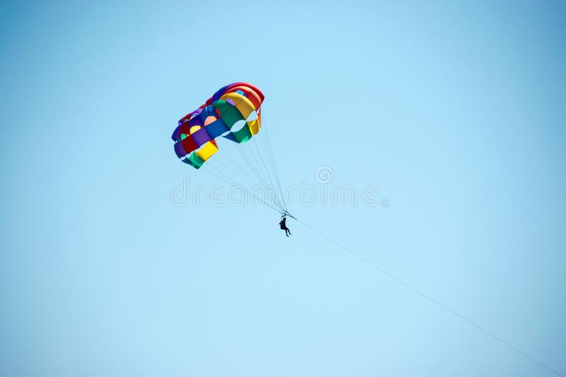 Parasailing. Blue sky and a parachute in rainbow colors. A popular type of outdoor activity at a beach resort royalty free stock photography