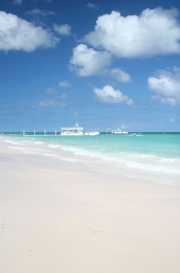 Parasailing and Boat in Ocean, Beach. Carribean Landscape - Parasailing, Pier and Ferry Boat in a Tropical Ocean, White Sand Beach (focus on the foreground waves stock photography