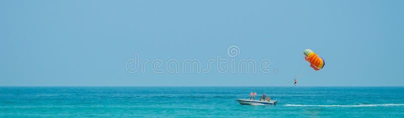 Parasailing Der Mann wird auf einem Boot geschleppt und fliegt mit einem Fallschirm über dem Wasser Panorama lizenzfreies stockfoto