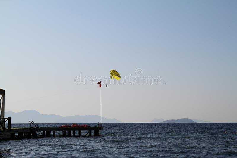 Parasailing is an extreme sport, people fly by parachute against the blue sky. stock photo