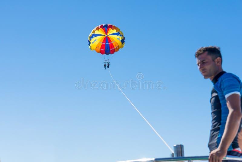 Parasailing felice delle coppie in spiaggia Dominicana di estate Coppie sotto il paracadute che appende metà di aria Avere divert immagini stock