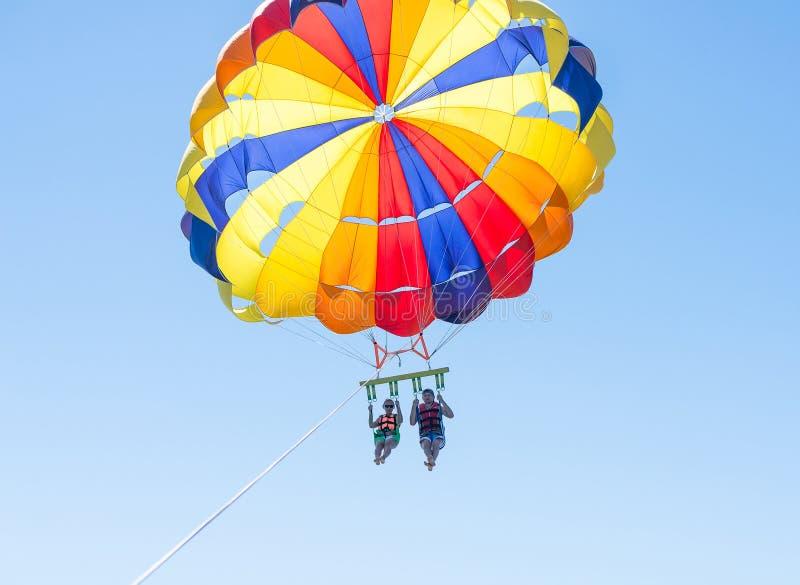 Parasailing feliz dos pares na praia Dominicana no verão Pares sob o meio do ar de suspensão do paraquedas Tendo o divertimento P imagem de stock