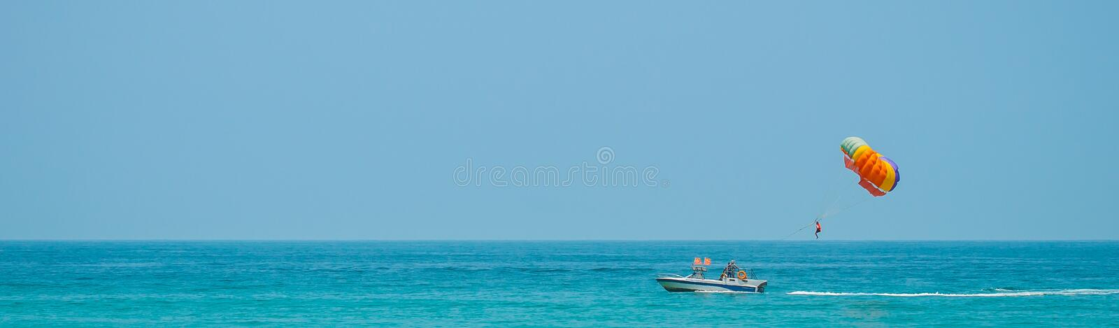 Parasailing. The man is towed on a boat and flies with a parachute over the water. Panorama royalty free stock photo
