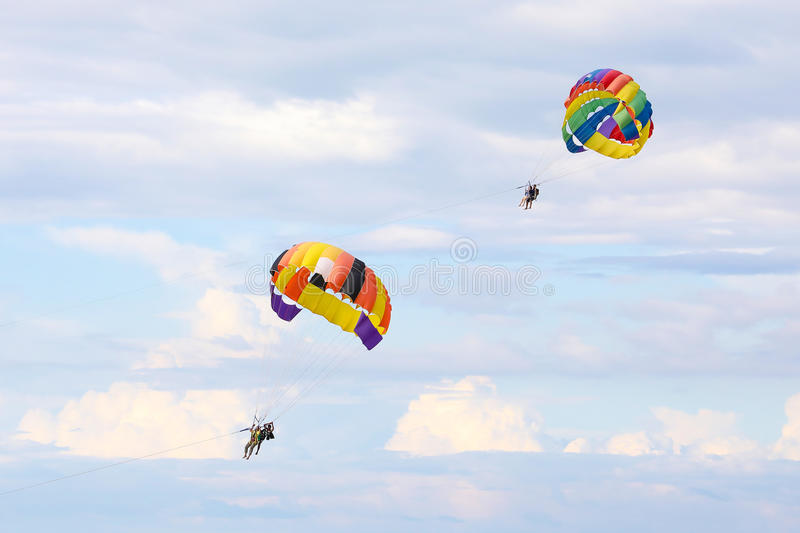 Two People Parasailing With Parachute On Blue Sky Stock
