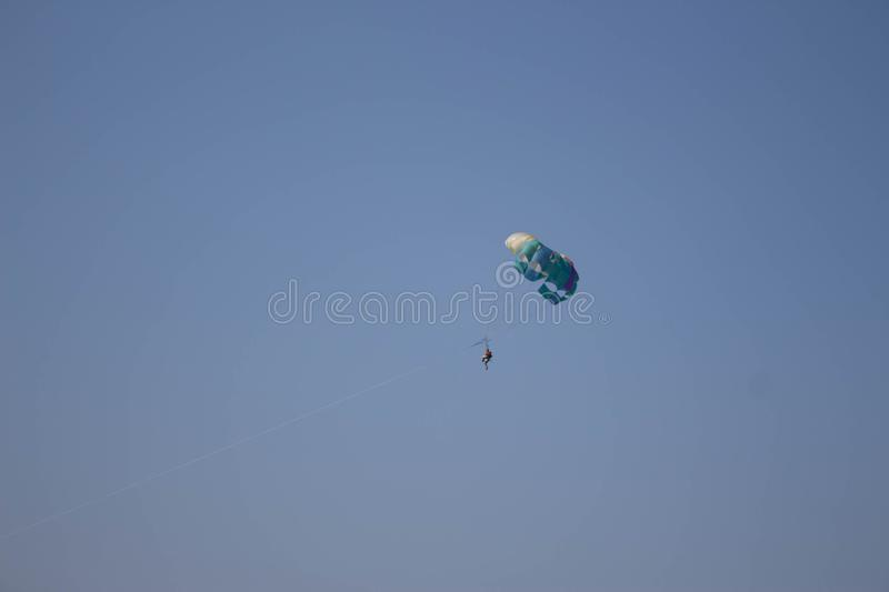 Parasailing is a popular pastime in many resorts around the world. The active form of relaxation. Parasailing - Fly with colorful parachute at the beach stock photography
