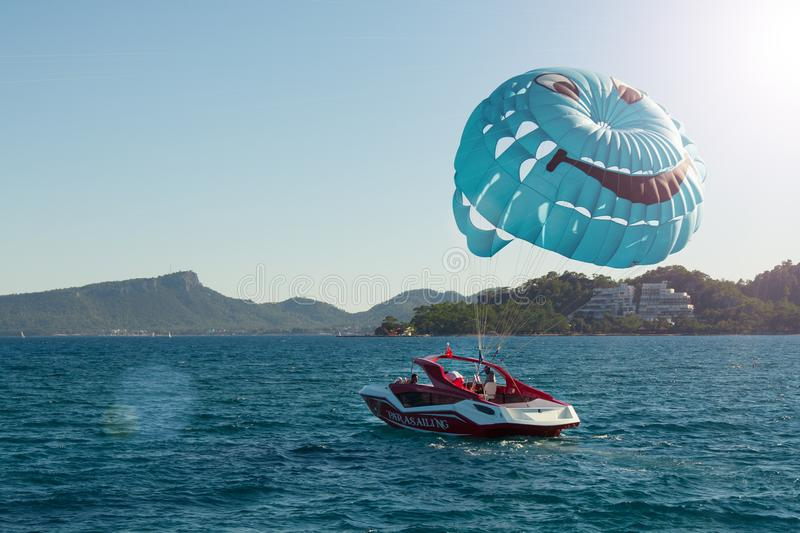 Parasailing, a red and white boat pulls a blue parachute with a smiley face stock photography