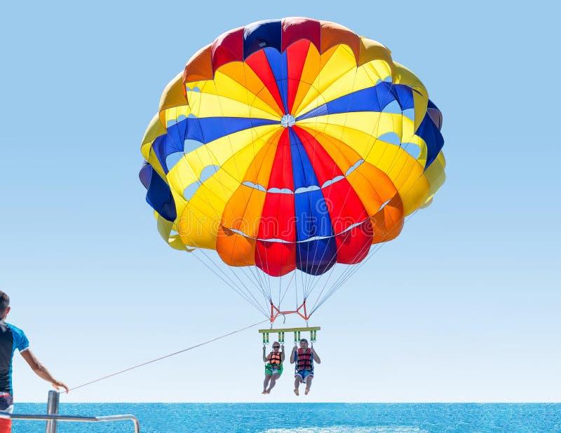 Parasailing sonriente feliz de los pares en la playa tropical en verano Recienes casados debajo del paracaídas que cuelga el medi fotos de archivo