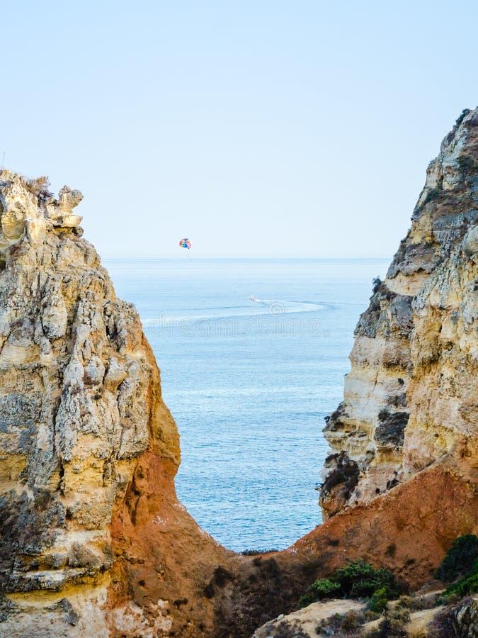 Parasailing, también conocido como parascending o parakiting en las costas del Algarve en Lagos, Portugal Rodeado con amarillo, o fotos de archivo libres de regalías