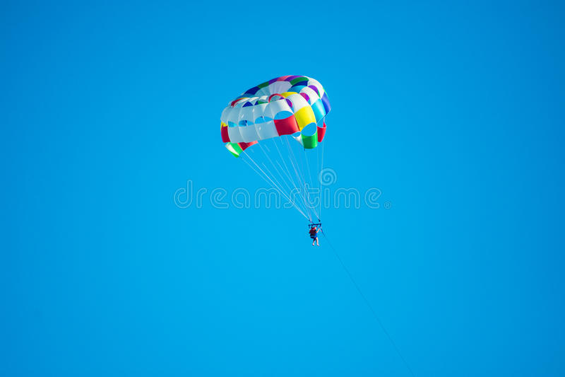 Parasailor on multi-colored parachute flying in blue clear sky, sunny weather, inspirational, summer, vacation stock images