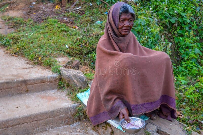 PARASHNATH, JHARKHAND, INDIEN 25. JANUAR 2017: Straßenporträt eines indischen Bettlers Dame, der auf der Seite einer Straße sitzt lizenzfreies stockfoto