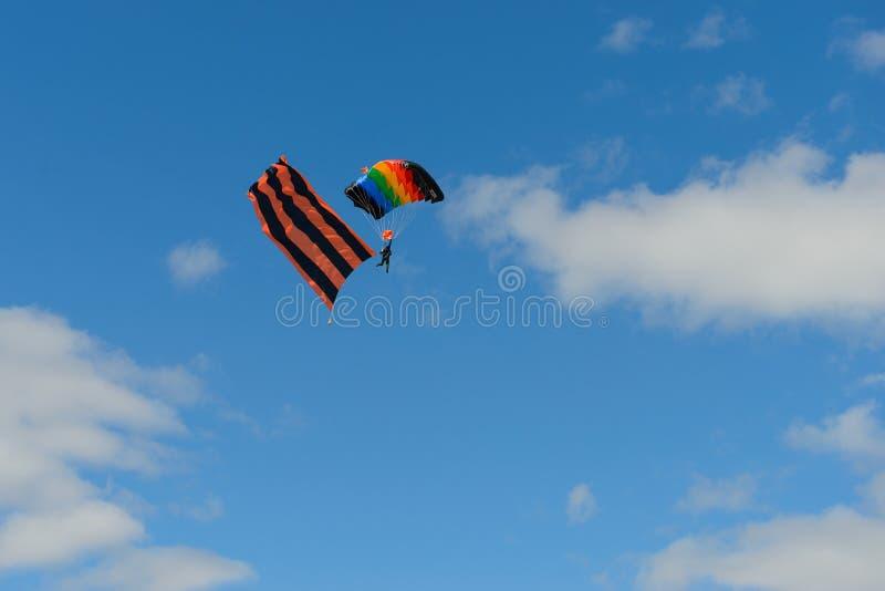 Parashutist mit einem mehrfarbigen Fallschirm und einer Flagge des St- Georgebandes stockfotos