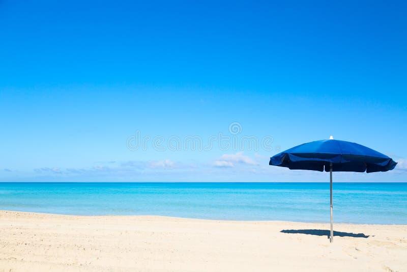 Parasol azul do guarda-chuva de praia na praia tropical Fundo das férias imagem de stock