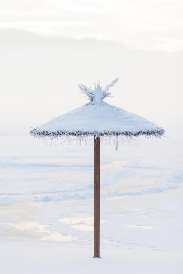 Download Parasol Covered With Snow On The Beach In The Winter Stock Photo - Image: 83709320