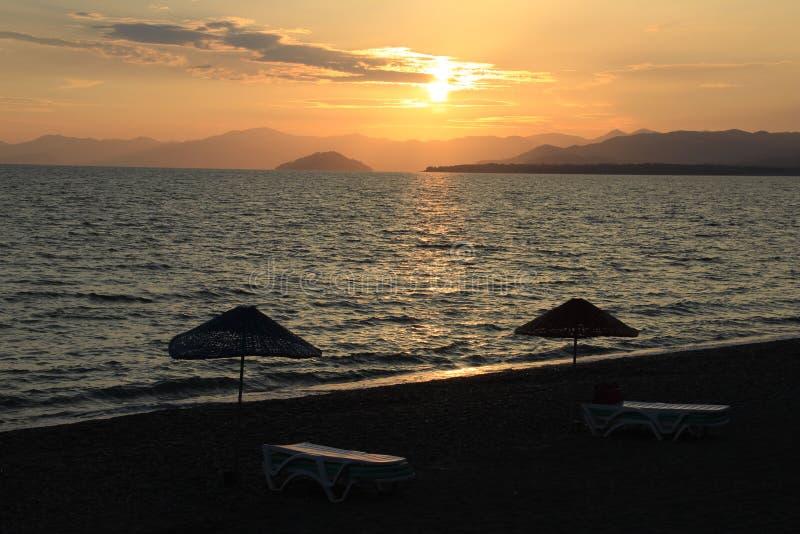 Parasol de canapé de Sun et en bambou sur la mer tropicale donnant sur les roches au coucher du soleil image stock