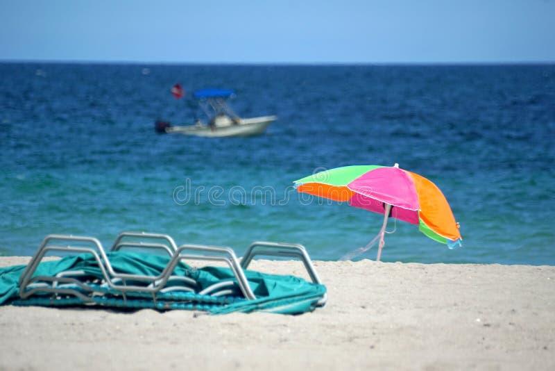 Parasol de playa en Dania Beach, con un barco de la zambullida en el fondo imagen de archivo libre de regalías