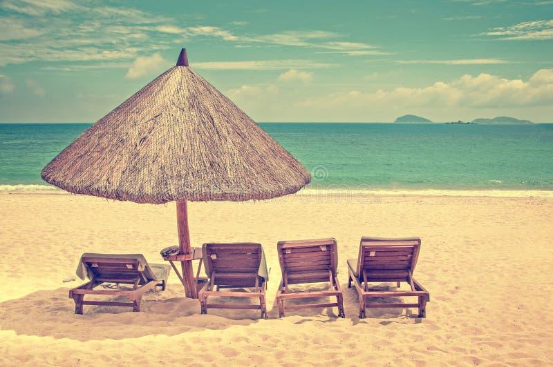 Parasol de playa de la paja y sillas de descanso de madera en un proceso perfecto del vintage de la playa fotografía de archivo