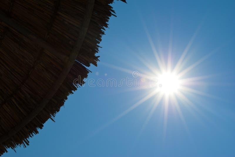 Parasol de playa y sol fotos de archivo