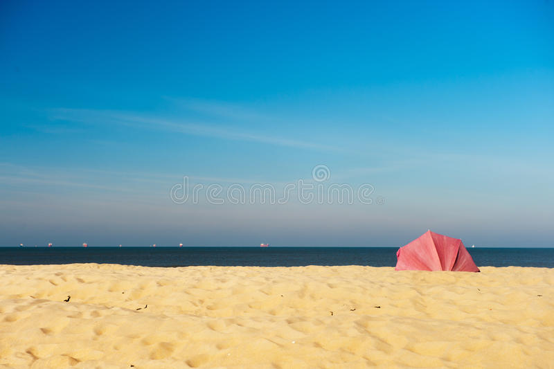 Parasol at the empty beach. Red parasol in the sand at the empty beach royalty free stock photography