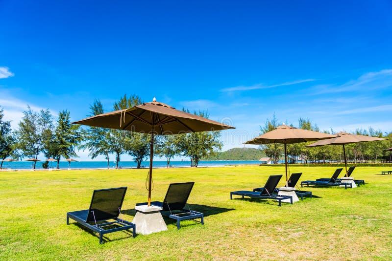 Parasol i krzesło na zielonej trawy prawie morza plaży fotografia stock