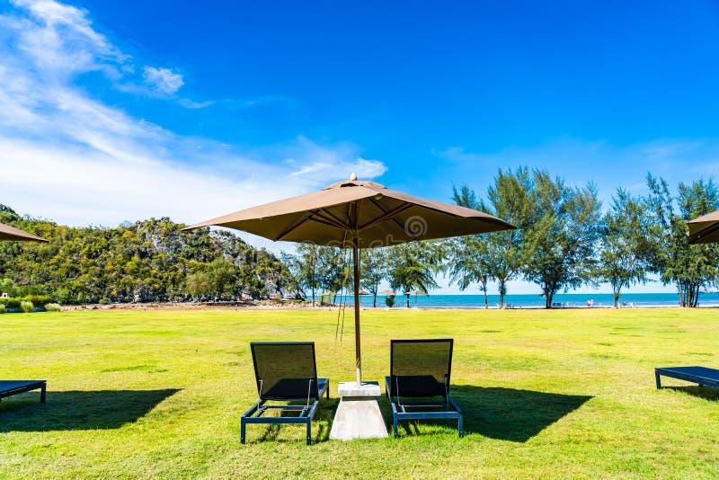 Parasol i krzes?o na zielonej trawy prawie morza pla?y obraz stock