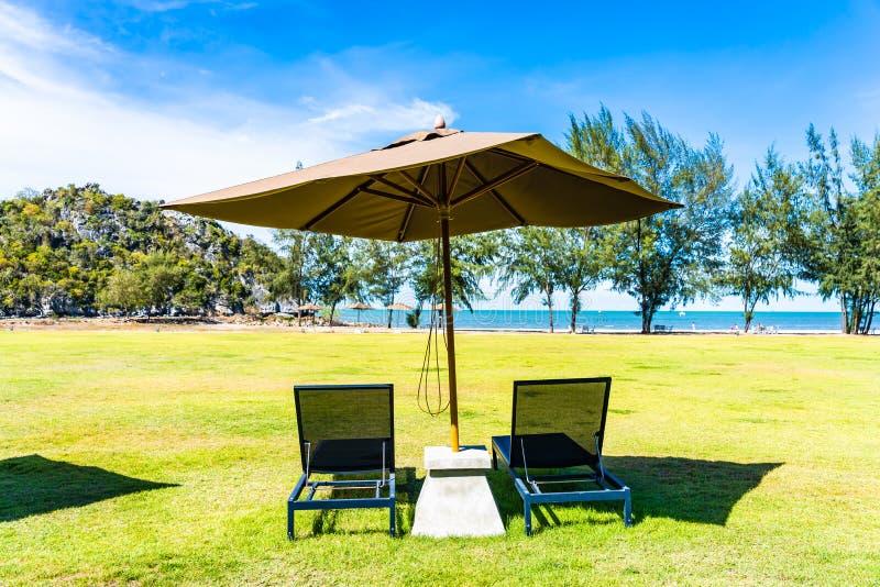 Parasol i krzes?o na zielonej trawy prawie morza pla?y zdjęcie stock