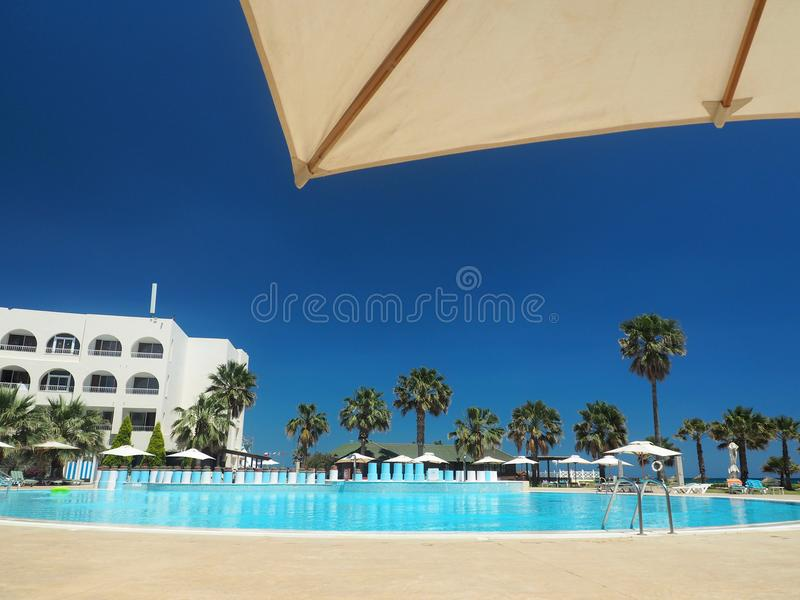 Parasol and palms, sky with clouds. travel concept stock photo