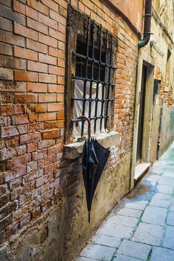 Parasol por la ventana en el fondo de una pared de ladrillo vieja fotografía de archivo