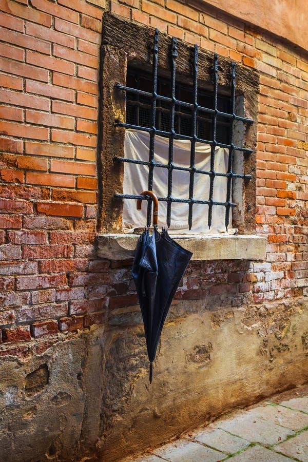 Parasol por la ventana en el fondo de una pared de ladrillo vieja fotos de archivo