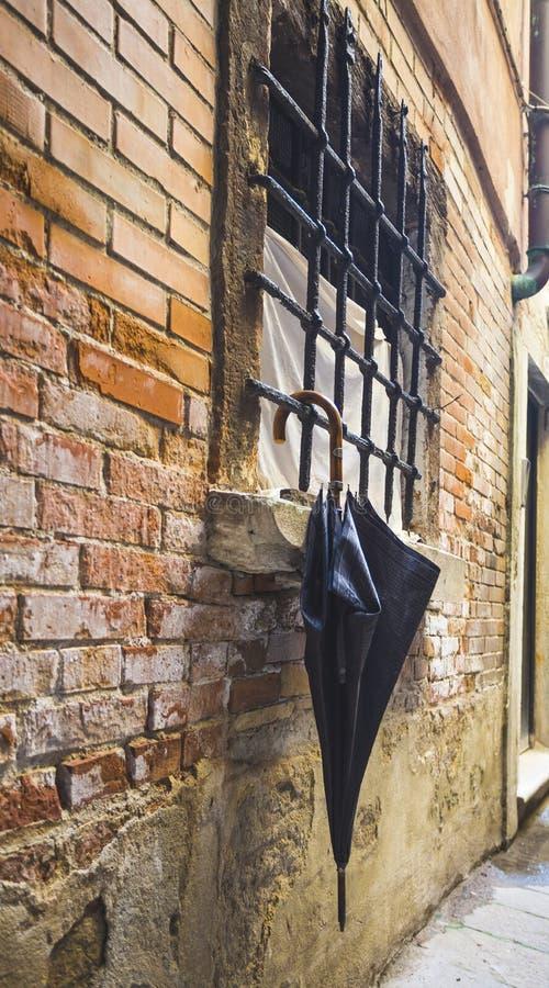Parasol por la ventana en el fondo de una pared de ladrillo vieja imágenes de archivo libres de regalías