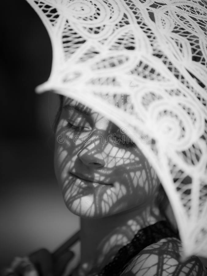 Parasol Shadow On Face. White Lace Parasol Tracing Geometric Patterns on Girls Face stock images