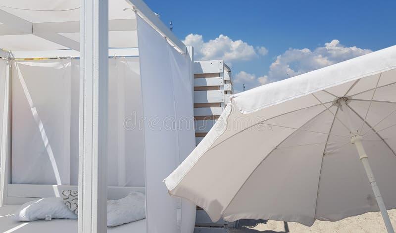Parasole bianco e parasole bianco sulla chiara sabbia della spiaggia fotografia stock libera da diritti