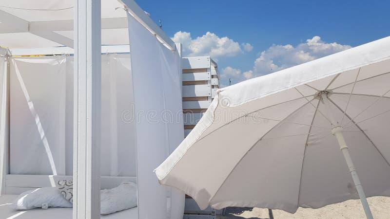 Parasole bianco e parasole bianco sulla chiara sabbia della spiaggia fotografia stock
